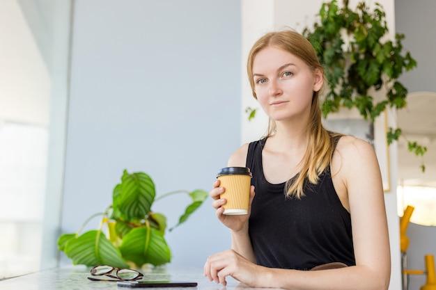 Hermosa mujer en café mediante teléfono móvil y mensajes de texto en las redes sociales