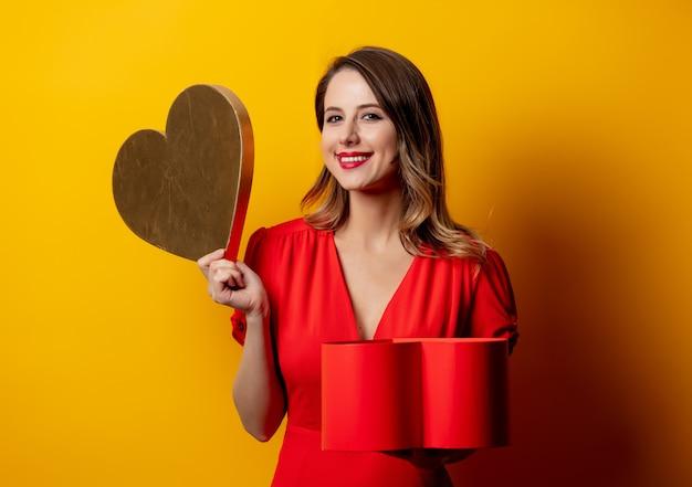 Hermosa mujer con caja en forma de corazón en la pared amarilla