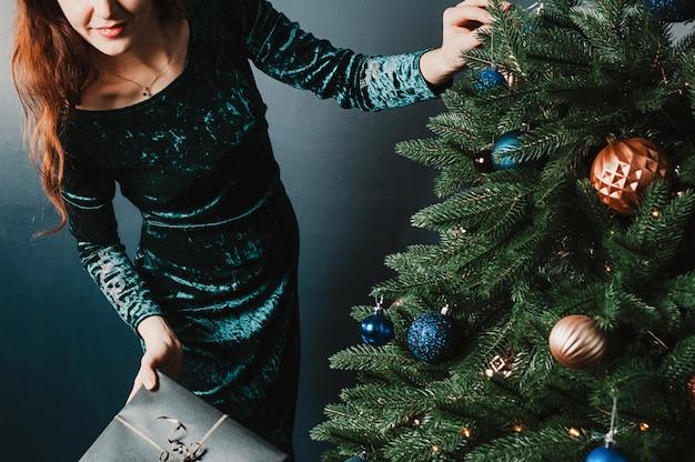 Hermosa mujer con caja de regalo cerca de árbol de navidad