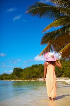 Hermosa mujer caliente en colorido sombrero para el sol y vestido caminando cerca de la playa del océano en un caluroso día de verano cerca de la palma