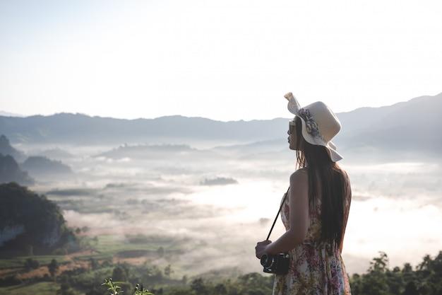 Hermosa mujer con una cámara de pie en la cima de la montaña