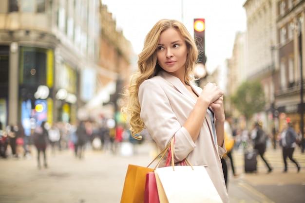 Hermosa mujer caminando en la calle, sosteniendo bolsas de compras