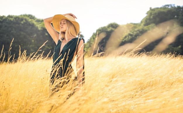 Hermosa mujer caminando en un campo de trigo y respirando profundamente