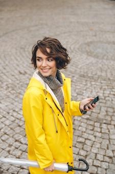 Hermosa mujer caminando sobre adoquines en el centro de la ciudad con teléfono móvil y paraguas en manos buscando amigo