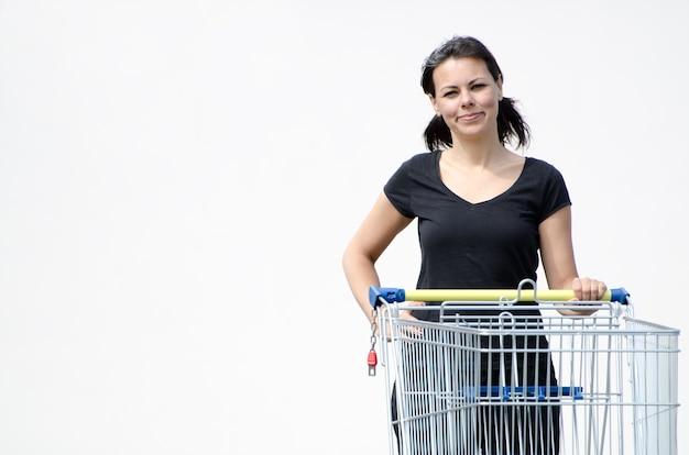 Hermosa mujer en una camisa negra sosteniendo un carrito de compras en blanco