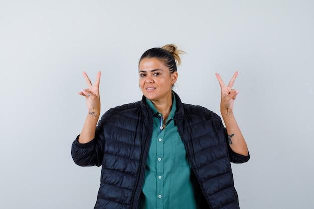 Hermosa mujer en camisa verde, chaqueta negra mostrando gesto de paz y mirando feliz, vista frontal.