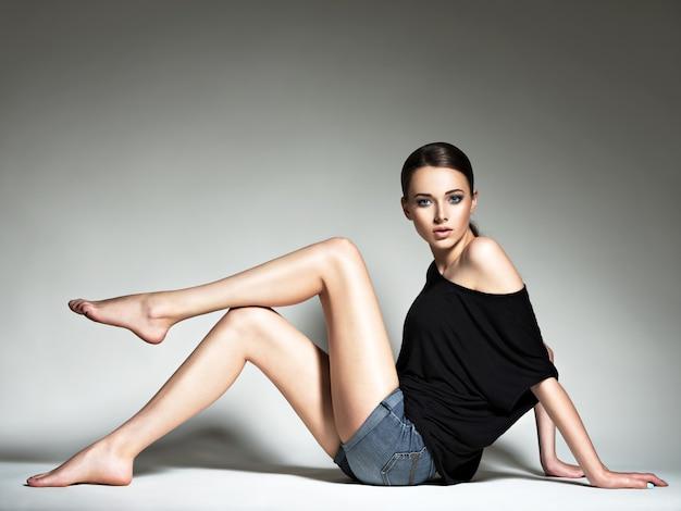 Hermosa mujer en camiseta negra y pantalones cortos de mezclilla.