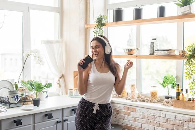 Hermosa mujer cantando en la cocina
