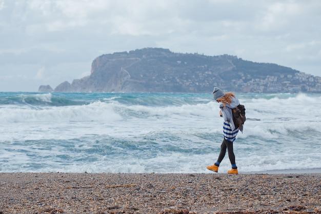 Hermosa mujer con capucha gris y sombrero caminando en la playa durante el día con mar
