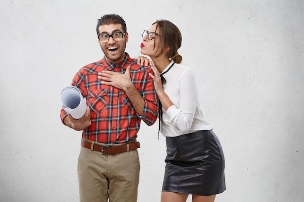 Hermosa mujer cariñosa va a besar a su novio. el hombre agradablemente sorprendido no espera tener tan buenas relaciones con su ex colega.