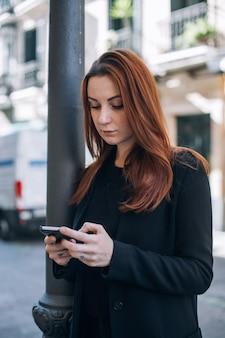 Hermosa mujer casual con cabello rojo y maquillaje natural se encuentra en la calle y mensajes de texto o charlas en su teléfono inteligente