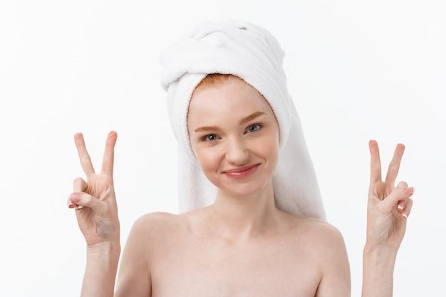 Hermosa mujer caucásica de aplicar la máscara en su rostro con signo de dos dedos.