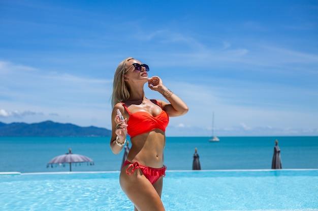 Hermosa mujer caucásica bronceada en forma bronce brillante piel en bikini con aceite de coco