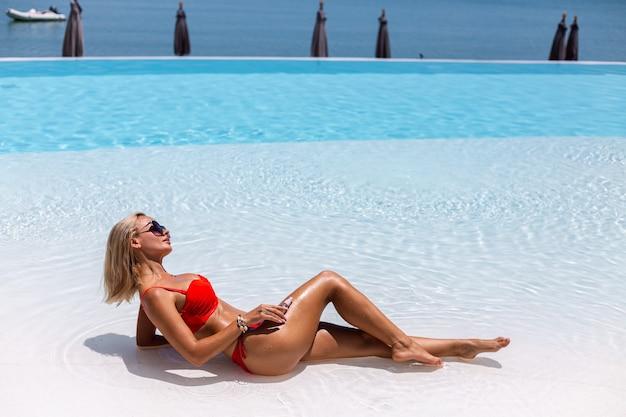 Hermosa mujer caucásica bronceada en forma bronceada piel brillante en bikini con aceite de coco en la piscina azul día soleado