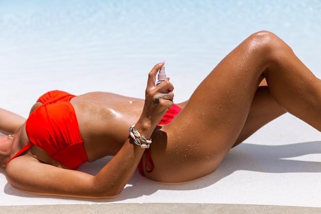 Hermosa mujer caucásica bronceada en forma bronceada piel brillante en bikini con aceite de coco