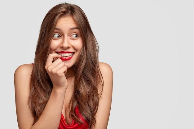 Hermosa mujer caucásica con cabello oscuro, sonrisa con dientes, usa maquillaje mínimo y lápiz labial rojo, mira con alegría a un lado, modelos contra la pared blanca con espacio libre para su texto promocional