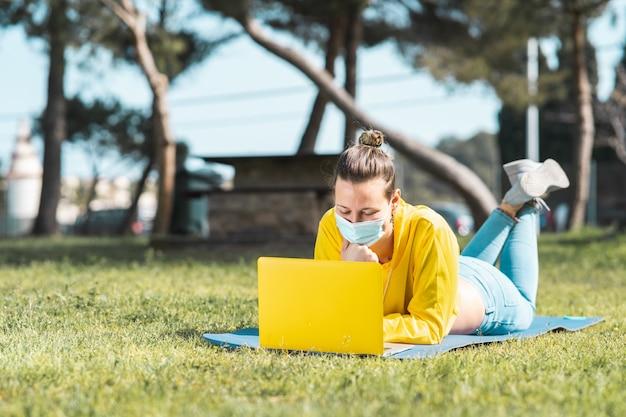 Hermosa mujer caucásica en una chaqueta amarilla y una mascarilla usando una computadora portátil en el parque