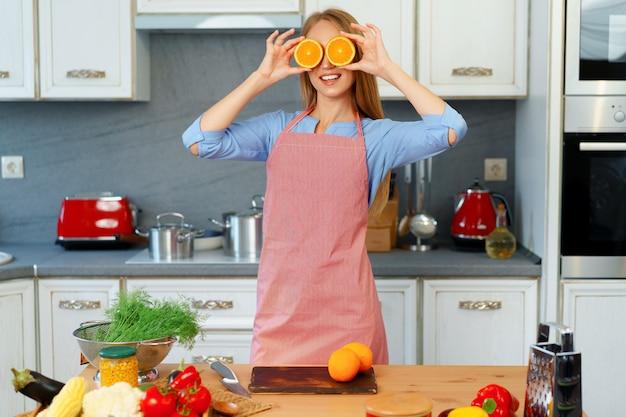 Hermosa mujer caucásica en delantal rojo sosteniendo naranjas maduras mientras está de pie en la cocina