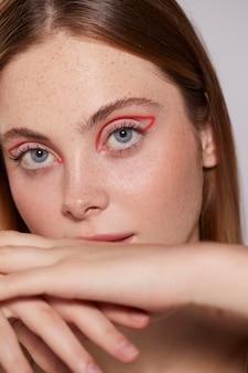 Hermosa mujer caucásica con delineador de ojos rojo