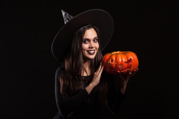 Hermosa mujer caucásica en un disfraz de bruja para fiesta de halloween. bruja aterradora. bruja sosteniendo una calabaza para halloween.