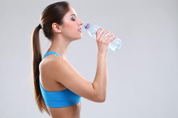 Hermosa mujer caucásica en fitwear con agua