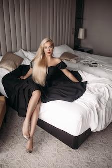 Hermosa mujer caucásica joven con cabello largo y rubio, cara bonita, maquillaje brillante, aretes brillantes en vestido largo negro se encuentra en la gran cama blanca