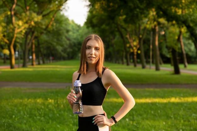 Hermosa mujer caucásica joven en desgaste físico trabajando en un parque.