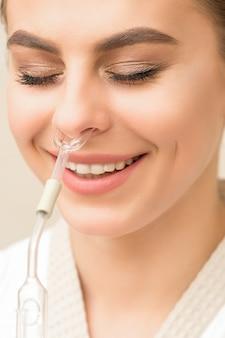 Hermosa mujer caucásica joven feliz recibiendo inhalador nasal con aceite esencial sonriendo en un spa
