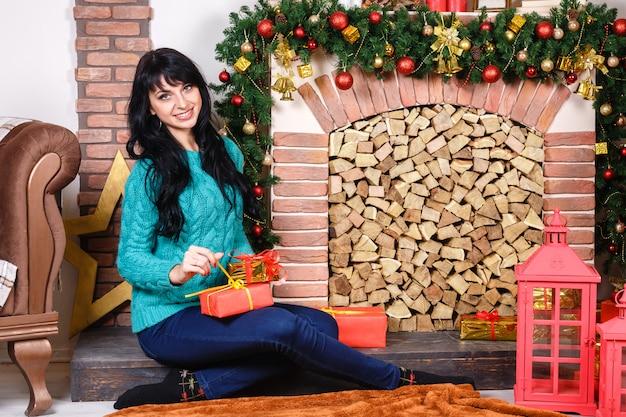 Hermosa mujer caucásica joven sentada cerca de una chimenea decorativa en un interior de navidad.