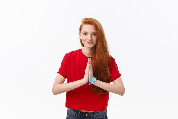 Hermosa mujer caucásica joven, tomados de la mano en namaste u oración, manteniendo los ojos cerrados mientras practica yoga.