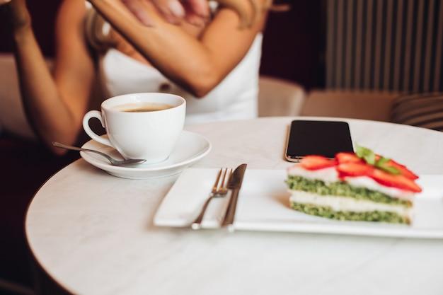 Hermosa mujer caucásica con largo cabello rubio ondulado se sienta en el sofá, bebe café