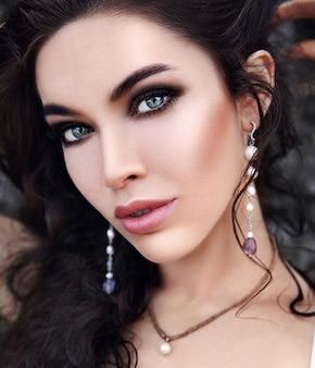 Hermosa mujer caucásica con maquillaje de noche y cabello largo oscuro al aire libre