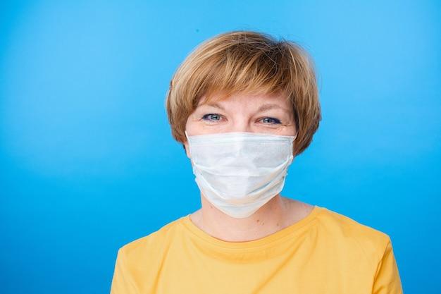 Hermosa mujer caucásica con máscara médica especial es feliz, retrato aislado sobre fondo azul.