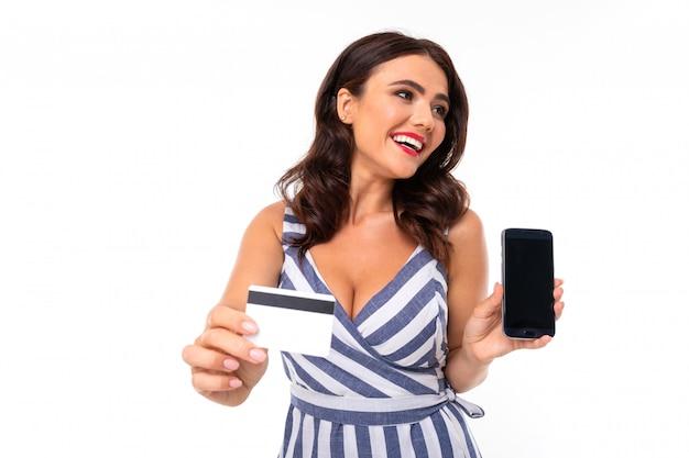 Hermosa mujer caucásica muestra teléfono y tarjeta, imagen aislada en blanco