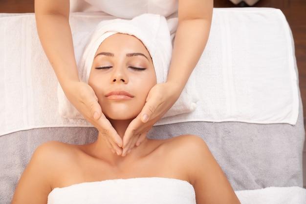 Hermosa mujer caucásica recibiendo masaje anti edad en el salón de spa