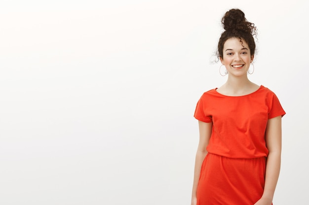 Hermosa mujer caucásica saliente en vestido rojo con pelo peinado, sonriendo ampliamente