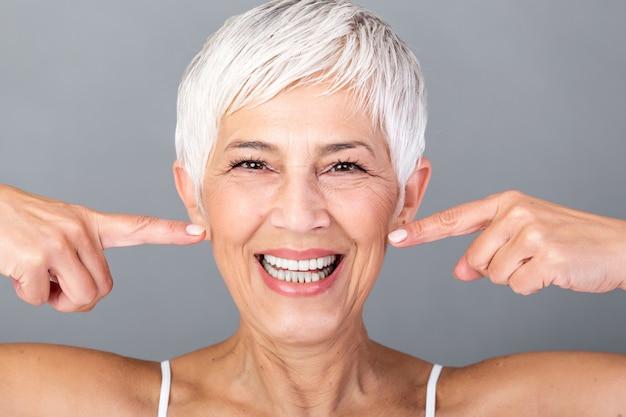 Hermosa mujer caucásica sonriente senior con cabello gris corto apuntando a sus dientes y mirando a cámara. fotografía de belleza.