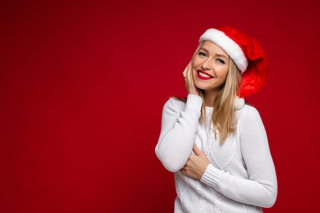 Hermosa mujer caucásica en suéter blanco y sombrero de navidad, imagen aislada sobre fondo rojo.