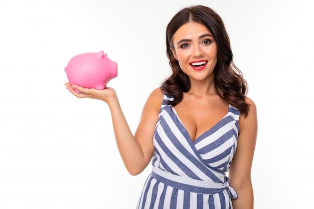 Hermosa mujer caucásica tiene una hucha de cerdo rosa y sonrisas, imagen aislada en blanco