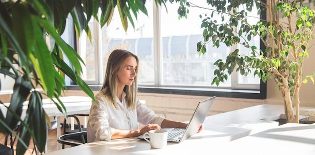 Hermosa mujer caucásica trabajando en una computadora portátil de forma remota en un espacio luminoso con plantas verdes.
