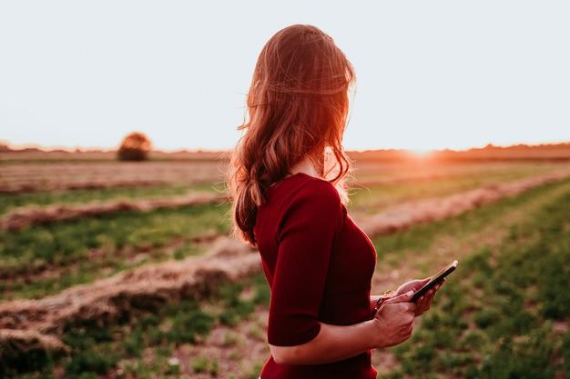 Hermosa mujer caucásica viendo el atardecer en el campo. usando el teléfono móvil. tecnología y estilo de vida al aire libre.