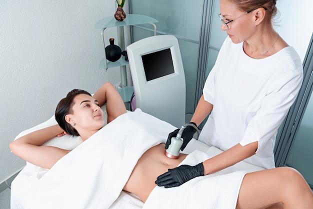 Hermosa mujer con cavitación, procedimiento para eliminar la celulitis en las piernas y el vientre en la clínica de belleza