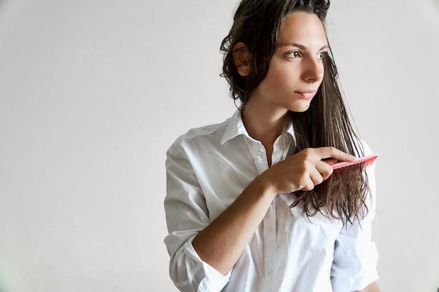 Hermosa mujer cepillando su cabello desordenado mojado después del baño con peine. problema del cabello fino