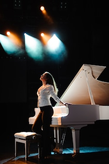 Hermosa mujer cerca de piano blanco om la escena