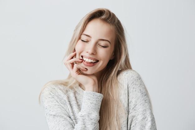 Hermosa mujer cerrando los ojos debido a la alegría, con cabello largo y rubio y una sonrisa amable. la mujer alegre sostiene la mano debajo de la barbilla, ha satisfecho la expresión de la cara. expresión facial y emociones positivas.