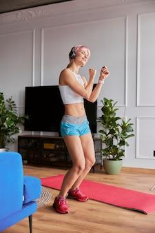 Hermosa mujer en chándal con auriculares baila en la sala de estar