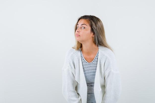 Hermosa mujer en chaqueta, camiseta de pie para escuchar con claridad y con curiosidad, vista frontal.