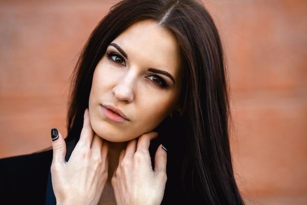 Hermosa mujer en una chaqueta junto a la pared