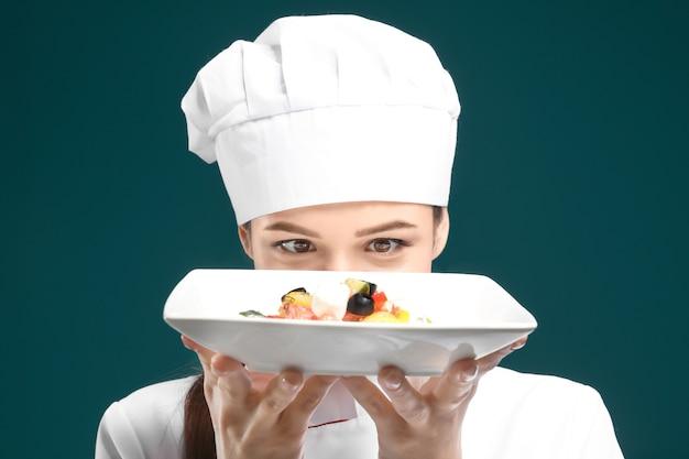 Hermosa mujer chef con plato con plato en verde