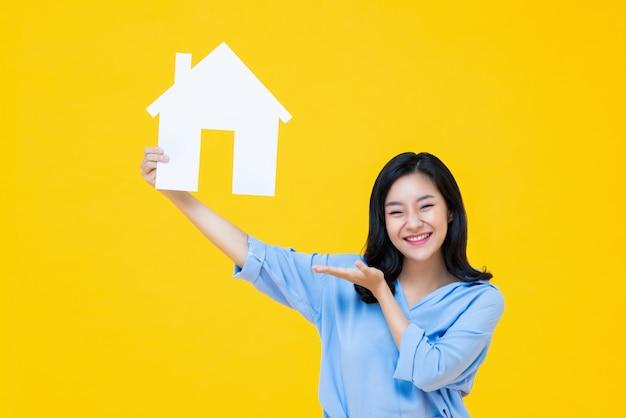 Hermosa mujer china felizmente sosteniendo el modelo de casa